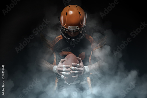 Photo American football player on a dark background in smoke in black and orange equipment