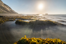 Amazing Las Brisas Beach An Awe Sea Coastline Landscape On A Wild Environment In Chile. The Sun Goes Down Over The Infinite Horizon While The Water Stream Push By The Waves Onto The Algae And Rocks