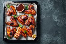 Roasted Chicken Wings In Barbecue Sauce With Sesame Seeds And Parsley In A Baking Tray On A Dark Table. Top View With Copy Space. Tasty Snack For Beer On A Dark Background. Flat Lay