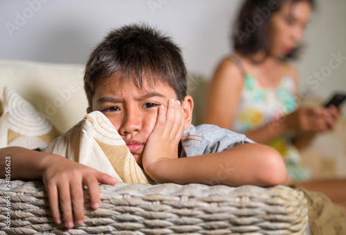 Fotografia young sad and bored Asian child at home couch feeling frustrated and unattended