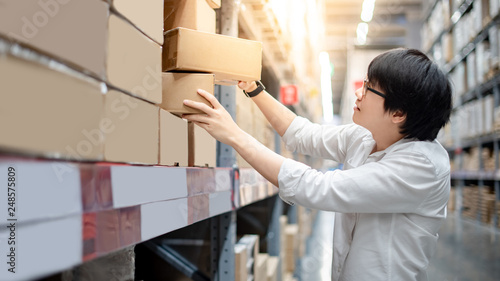 Young Asian shopper man picking cardboard box package from product shelf in warehouse Fototapeta