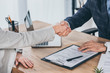 cropped view of shaking hands businessman and woman over table in office, compensation concept