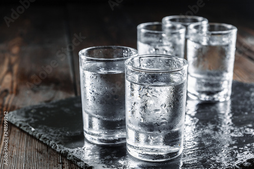 Fotografija Vodka in shot glasses on rustic wood background
