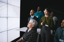 Business Group Having A Discussion During A Conference, Looking A Large Video Wall With Charts And Graphs