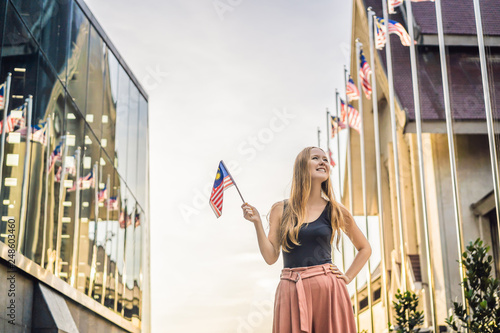 Young woman travels in Malaysia. Holds the Malaysian flag Wallpaper Mural