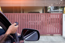 Woman In Car, Hand Opening The Automatic Gate By Using Remote Control. The Auto Door And Security System Concept.