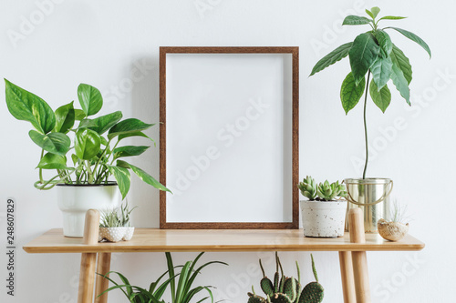 Vászonkép Scandinavian room interior with mock up photo frame on the brown bamboo shelf with beautiful plants in differents hipster and design pots