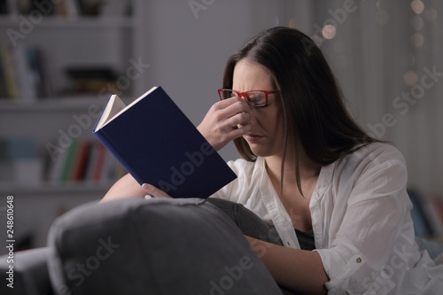 Fotomural Lady with eyeglasses suffering eyestrain reading book in the night