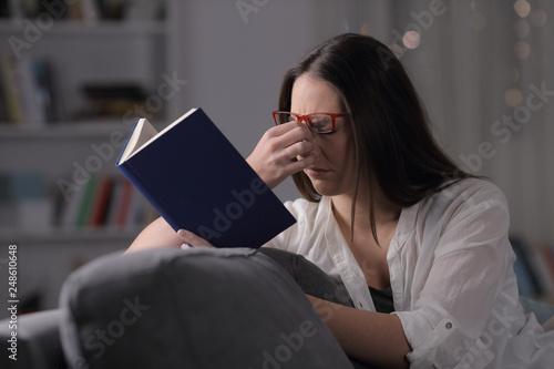Fotografía  Lady with eyeglasses suffering eyestrain reading book in the night