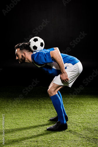sportsman in uniform training with ball on grass isolated on black