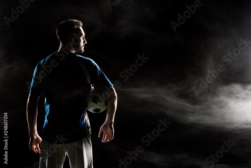 Slika na platnu silhouette of football player holding ball on black with smoke