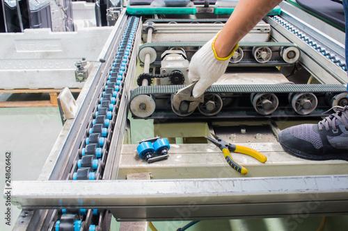 Obraz na płótnie worker maintenance and repair conveyor belt in factory