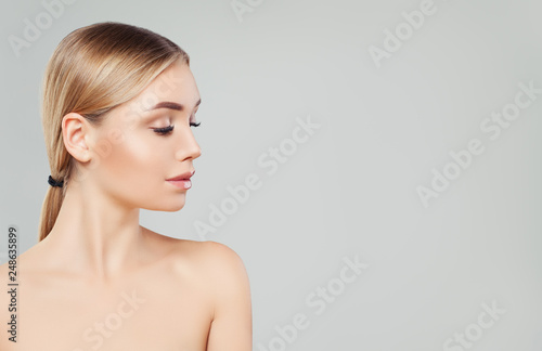 Fototapeta Beautiful blonde woman face, female profile on white background. Facial treatment, skin care and cosmetology concept obraz