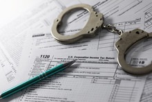 Tax Evasion And Avoidance Concept. Annual Income Declaration Form And Handcuffs