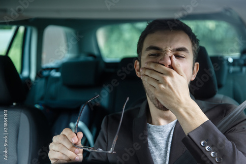 Fotografie, Obraz  Sleepy young guy yawns while covering his mouth with his left hand