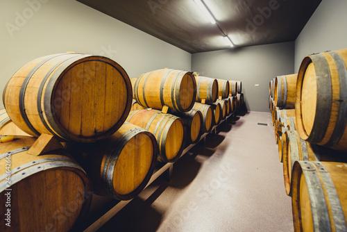 Fotografie, Obraz  Wooden wine barrels stacked in modern winery cellar in Spain.