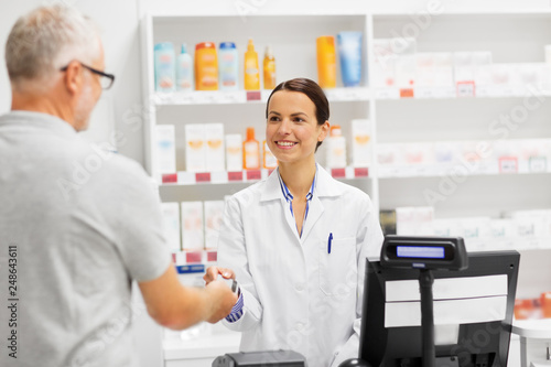 Photo sur Toile Pharmacie medicine, pharmaceutics, healthcare and people concept - happy smiling female apothecary taking senior customer credit card at pharmacy cash register