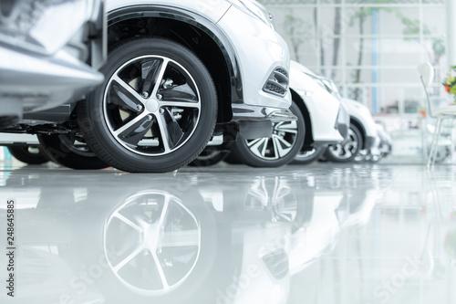 Samochody na sprzedaż, przemysł motoryzacyjny, parking samochodowy. Rzędy zupełnie nowych pojazdów oczekujących na nowych właścicieli, na posadzce epoksydowej w serwisie nowych samochodów