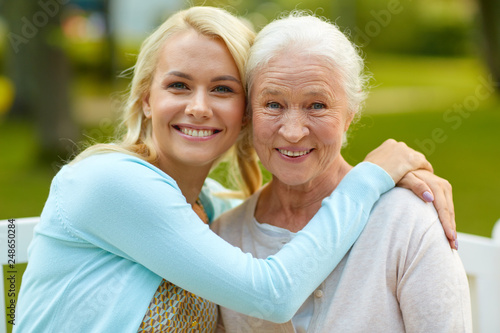 Obraz family, generation and people concept - happy smiling young daughter with senior mother sitting on park bench and hugging - fototapety do salonu