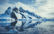 Ice Covered Mountains In Polar Ocean. Winter Antarctic Landscape In Blue And White Tints. The Mount's Reflection In The Crystal Clear Water. The Cloudy Sky Over The Massive Glacier. Travel Wild Nature