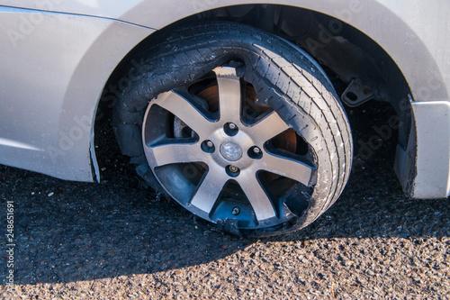 Vászonkép Car tire that has a blowout with rim and car damage