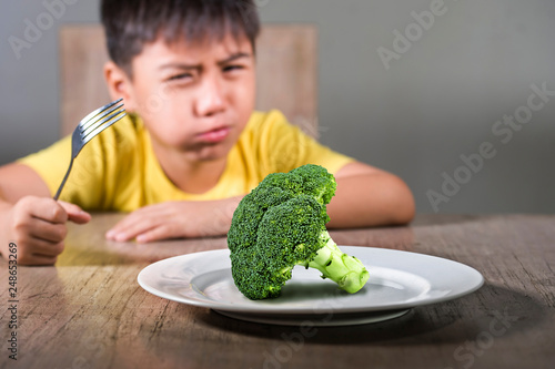 Obraz na plátne disgusted child refusing to eat healthy green broccoli feeling upset in kid nutr