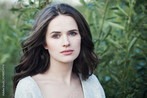 Young woman outdoors on green spring leaves background. Beauty girl face closeup