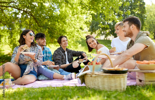 Fototapeta friendship, leisure and fast food concept - group of happy friends eating sandwi