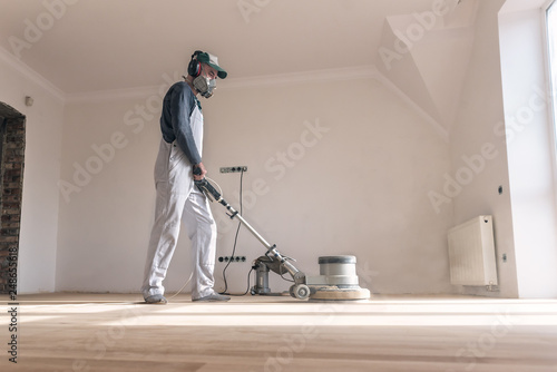 Obraz Man clean the parquet with polishing machine - fototapety do salonu
