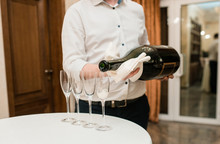 Sommelier Waiter Pours Big Giant Bottle Of Champagne In A Transparent Glass On A White Table
