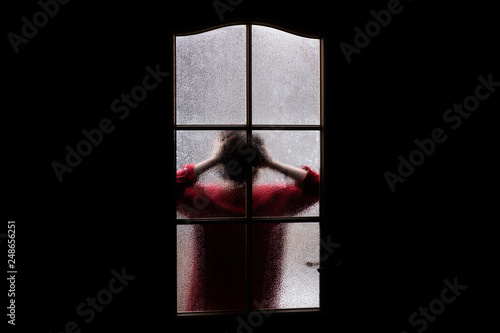 Fotografia Dark silhouette of girl in red behind glass