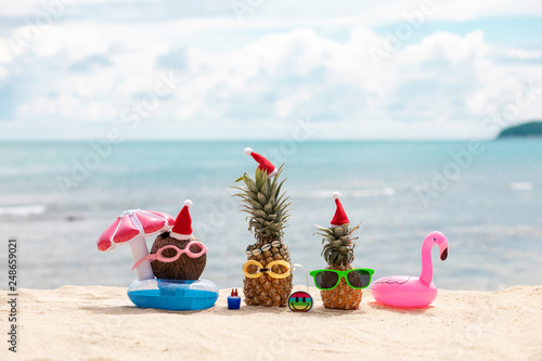 af732c59 funny attractive pineapples and coconut in stylish sunglasses on the sand  against turquoise sea. Wearing