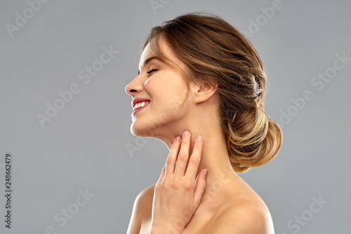 beauty and people concept - smiling young woman touching her neck over grey back Wallpaper Mural
