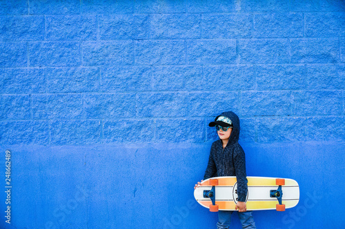 Fotografering  Little skater plays with the board on a blue wall