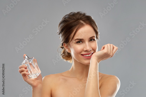 Fototapeta perfumery, beauty and luxury concept - happy smiling young woman smelling perfume from her wrist over gray background obraz