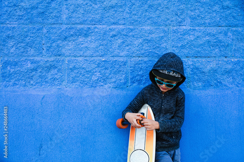 Valokuva  Little skater plays with the board on a blue wall