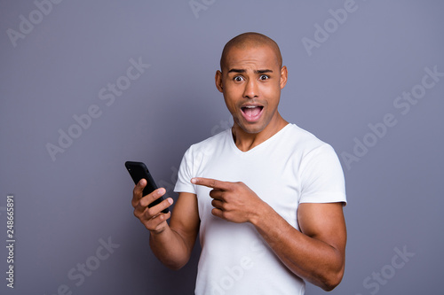 Close up photo strong healthy dark skin he him his macho bald head telephone arms amazed new android version mouth opened in delight wearing white t-shirt outfit clothes isolated grey background