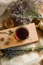 Bunches Of Dried Herbs And Jar Of Fresh Honey Lying On Blanket Near Board With Cup Of Hot Tea And Cubes Of Sugar