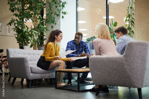 Fototapety, obrazy: Positive creative business team in casual clothing sitting on sofas and discussing sales statistics while analyzing papers in office