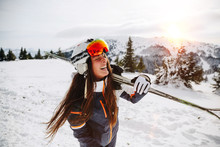 Portrait Of Beautiful Woman With Ski And Ski Suit In Winter Mountain