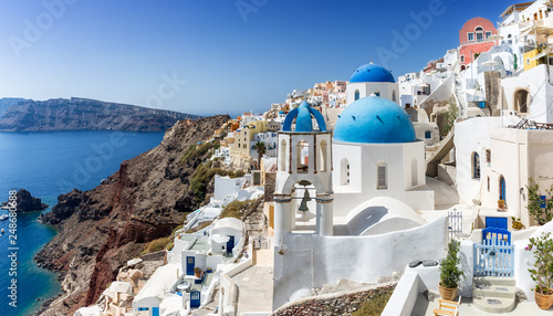 Poster Santorini Blick auf die weißen Häuser und die blauen Kuppeln der Kirchen in Oia auf Santorini, Kykladen, Griechenland