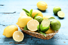 Lemons And Limes With Green Leafs In Basket On Blue Wooden Table