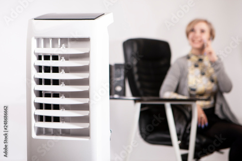 Obraz A woman works in an office with air conditioning. Air conditioning facilities. Outdoor air conditioning. Air purifier in the office. Humidifier. - fototapety do salonu