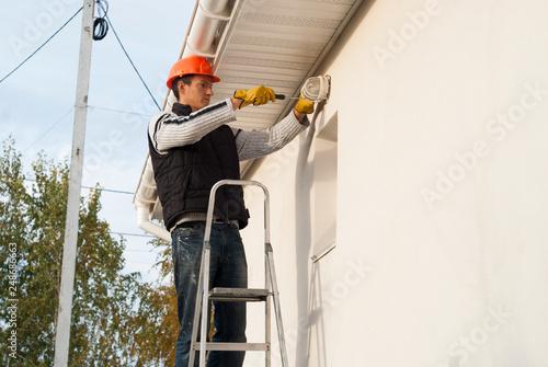 Fotografia  electrician installs a lamp