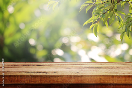 Wooden table and blurred green nature garden background.