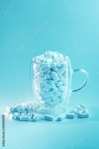 Fotomural White tablets falling out of glass mug