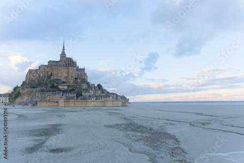 Photo  Monastery Mont Saint-Michel at low tide sunset blue twilight abbey sand horizon