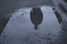 Male Silhouette Reflected In Dark Puddle Cloud Ominous Spooky