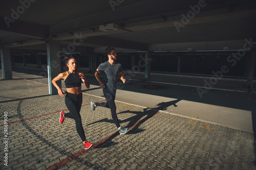 Fotografia  Young sports couple running in the urban environment