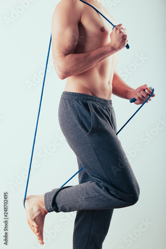 Fotografia  Young man holding skipping rope, doing exercises at home